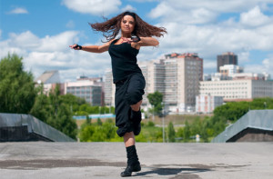 Beautiful teenage girl dancing in modern style over urban city landscape
