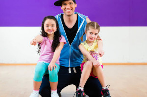 Young dancing teacher trainin children in modern zumba group choreography