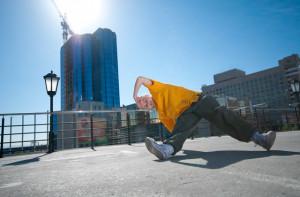 Teenage hip-hop girl dancing over urban city landscape