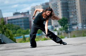Beautiful teenage girl dancing hip-hop over urban city landscape