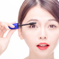Chinese woman putting mascara on eyelashes